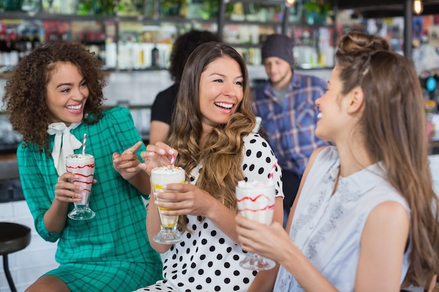 Vriendinnen genieten van terwijl het hebben van een drankje in restaurant