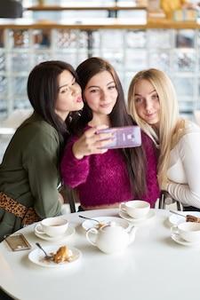 Vriendinnen hebben plezier in café, het drinken van thee en het maken van selfie