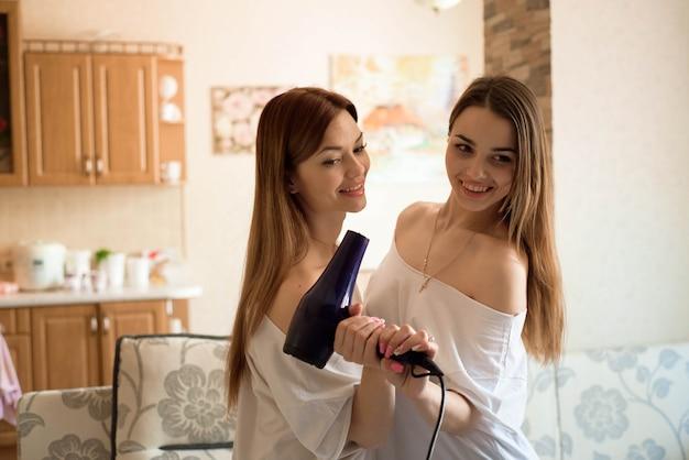 Vriendinnen hebben plezier, zingen en spelen samen thuis.