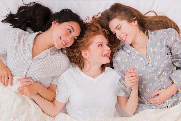 Vriendinnen in bed gelegd en hand in hand