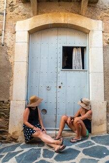 Vriendinnen in de zomer genieten van de vakantie. blanke meisjes met strohoeden die lachend naast een deur zitten en genieten van de hitte tijdens de vakantie