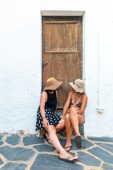 Vriendinnen in de zomer genieten van de vakantie. blanke meisjes zitten bij een deur en genieten van de hitte op vakantie