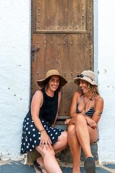 Vriendinnen in de zomer genieten van de vakantie. kaukasische meisjes glimlachend zittend in een deuropening genietend van de hitte op vakantie