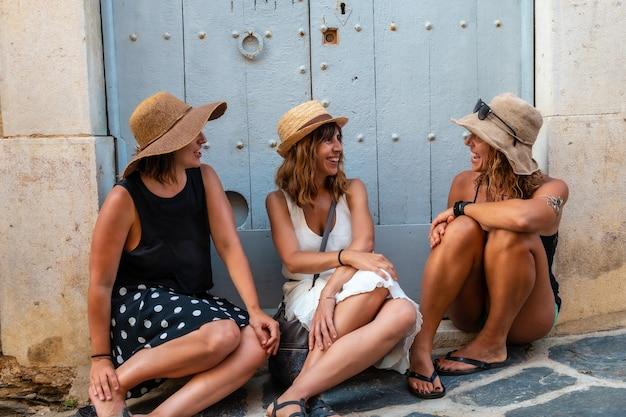 Vriendinnen in de zomer genieten van de vakantie. twee zussen met een zus zittend op een houten deur genietend van de middellandse zee