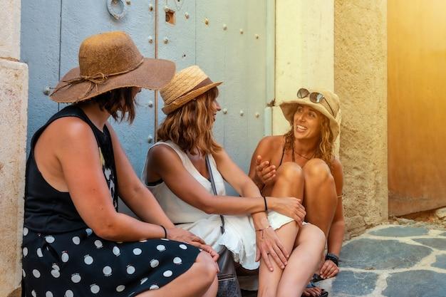Vriendinnen in de zomer genieten van de vakantie. twee zussen met een zus zittend op een houten deur in de middellandse zee bij zonsondergang