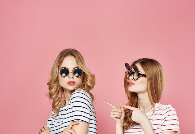 Vriendinnen in gestreepte t-shirts communicatie emoties levensstijl roze achtergrond