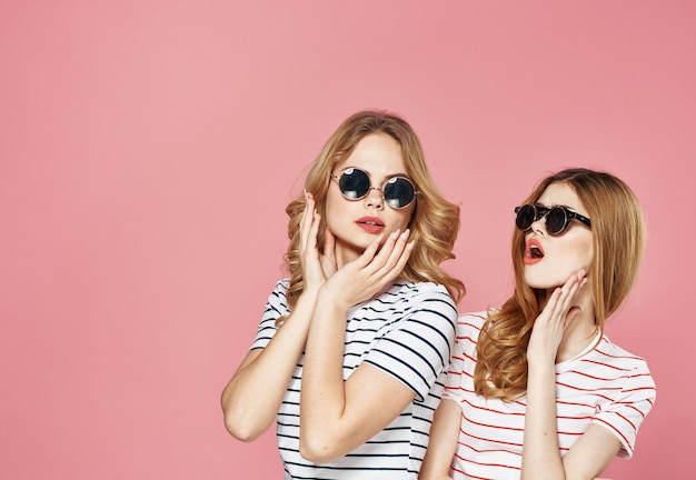 Vriendinnen in gestreepte t-shirts communicatie emoties levensstijl roze.