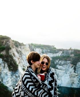 Vriendinnen knuffelen samen onder deken op de top van de berg