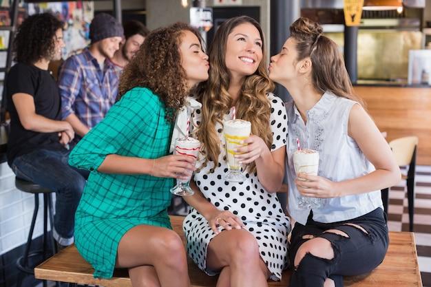 Vriendinnen kussen vrouw in restaurant