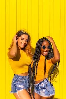 Vriendinnen levensstijl, zwart meisje met lange vlechten en blonde blanke in gele shirts en korte spijkerbroek op een gele muur. plezier hebben in de stad op een muur met gele kleur