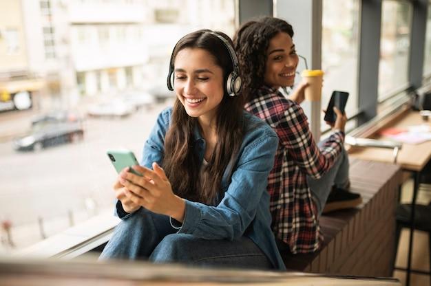 Vriendinnen luisteren naar muziek op de koptelefoon