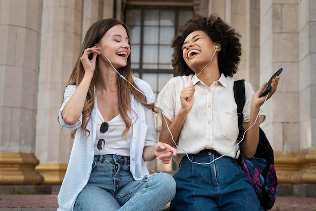 Vriendinnen luisteren naar muziek op oortelefoons van smartphone buitenshuis