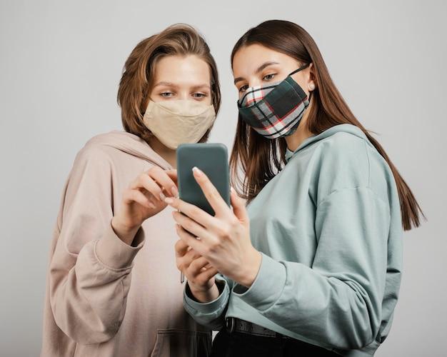 Vriendinnen maskers dragen en telefoon gebruiken