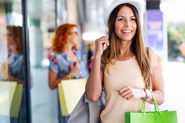Vriendinnen met boodschappentassen die plezier hebben tijdens het winkelen in een winkelcentrum, winkels