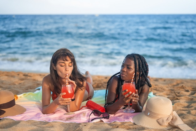 Vriendinnen met cocktails die op het strand rusten