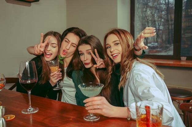 Vriendinnen met een drankje aan de bar. ze zitten aan een houten tafel met cocktails. ze dragen vrijetijdskleding.
