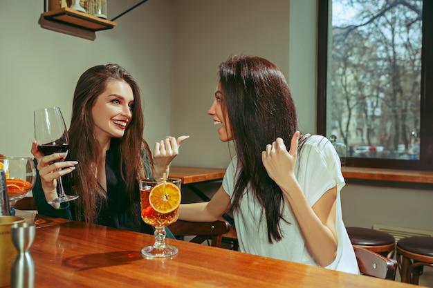 Vriendinnen met een drankje aan de bar. ze zitten aan een houten tafel met cocktails.