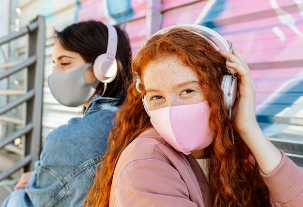 Vriendinnen met gezichtsmaskers buiten luisteren naar muziek op de koptelefoon