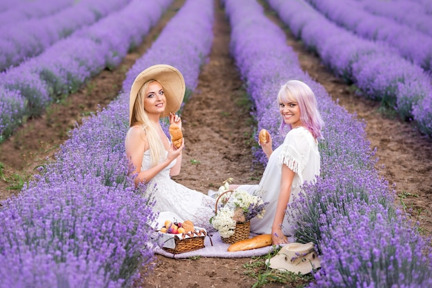 Vriendinnen met hoeden en een witte jurk zitten in een lavendelveld. picknick in lavendel. croissants en broodjes in de hand.