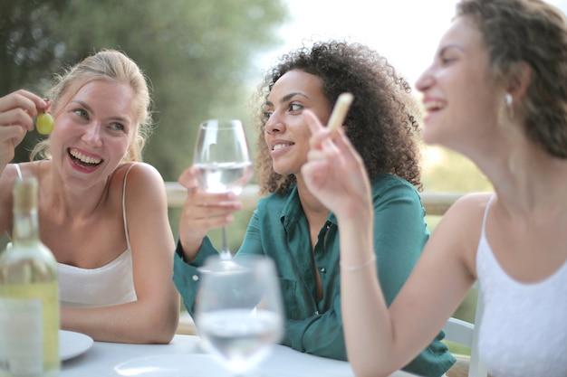Vriendinnen naast elkaar wijn drinken en lachen