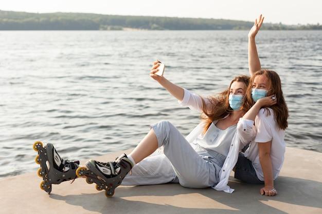 Vriendinnen nemen selfie bij meer met medische maskers en rolschaatsen