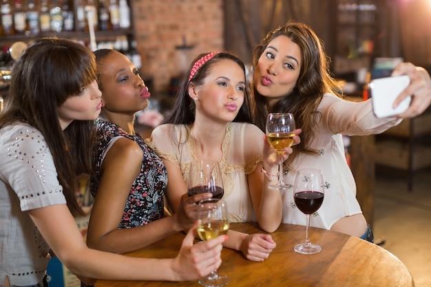 Vriendinnen nemen selfie terwijl wijnglazen