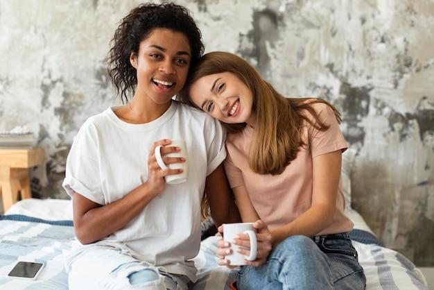Vriendinnen omarmd met koffiemokken thuis