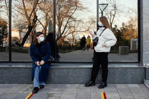 Vriendinnen ontmoeten bij koffie terwijl ze maskers dragen