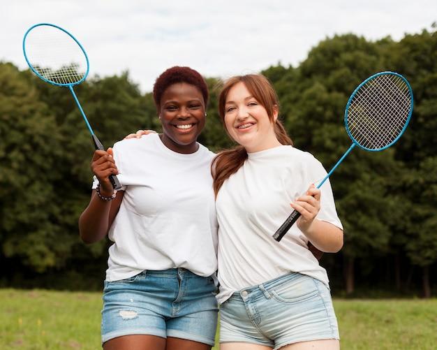 Vriendinnen poseren buitenshuis met rackets