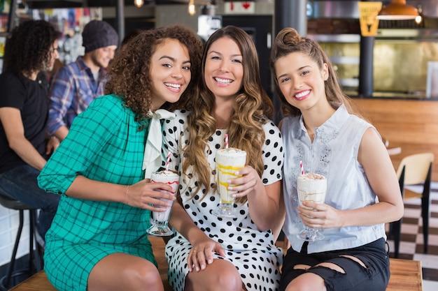 Vriendinnen poseren met smoothies in restaurant