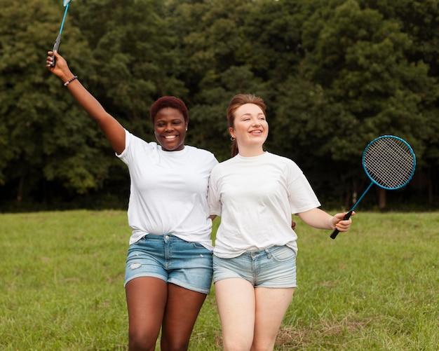 Vriendinnen poseren samen buitenshuis met rackets