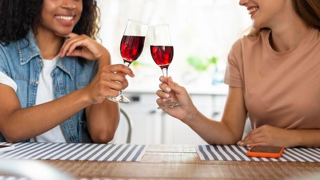 Vriendinnen roosteren een glas wijn in de keuken
