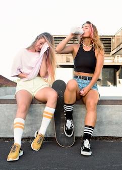 Vriendinnen rusten terwijl ze gehydrateerd raken bij de schaatsbaan