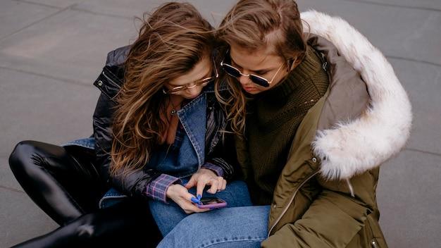 Vriendinnen samen plezier buitenshuis met smartphone