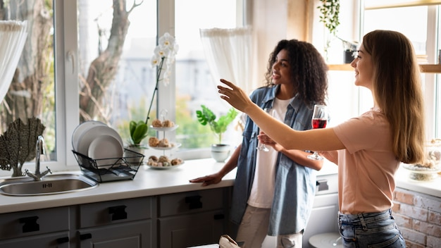 Vriendinnen socialiseren in de keuken over wijn