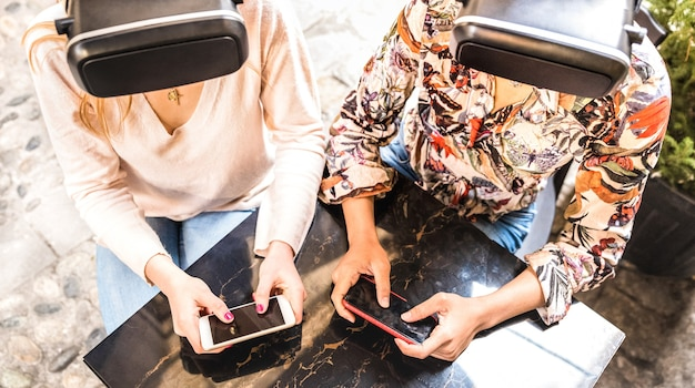 Vriendinnen spelen op vr-bril buiten - virtuele realiteit en draagbare technologie