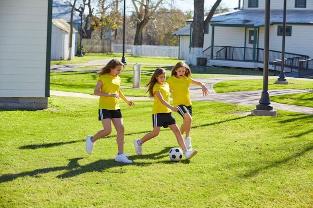 Vriendinnen tieners spelen voetbal in een park