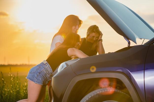 Vriendinnen vast in het veld tijdens roadtrip, controleren en proberen voertuig met open motorkap te repareren in zonsonderganglicht, reisavonturen