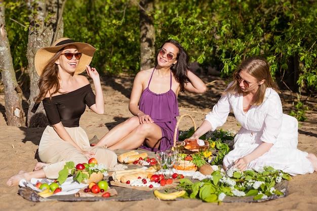 Vriendinnen vieren feest in de zomer tijdens een picknick