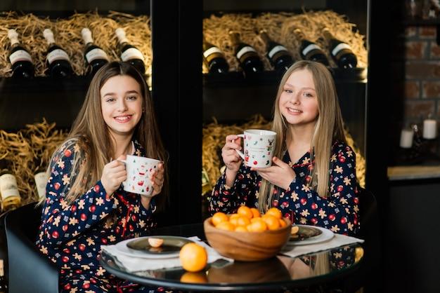 Vriendinnen vieren oudejaarsavond en kerstmis en eten mandarijnen op het bed. er zijn cadeautjes en versierde dennentakken met gouden ballen.