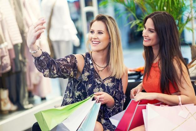 Vriendinnen winkelen voor kleding in de winkel