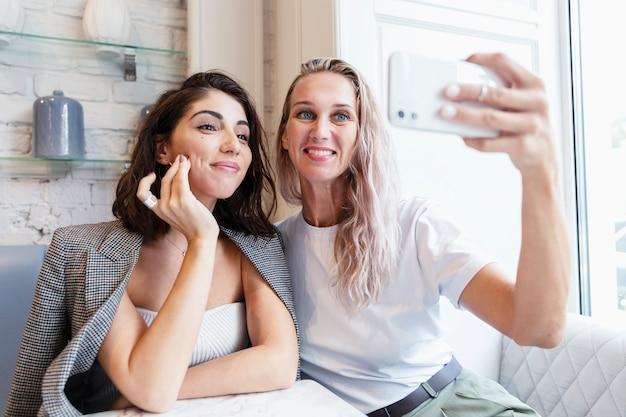 Vriendinnen zitten aan een tafel in een café en maken foto's