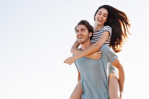 Vriendje die lachende vriendin bij het strand draagt