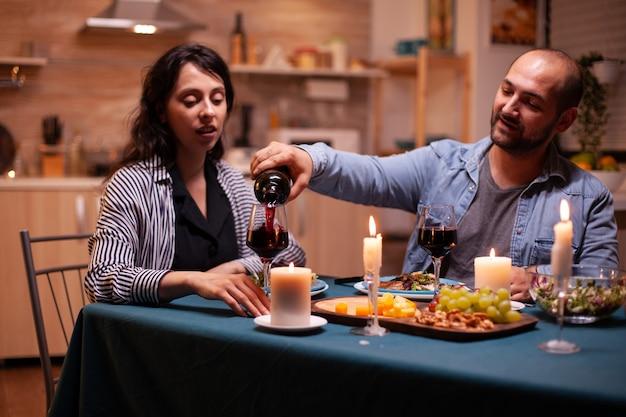 Vriendje viert relatie met vrouw in eetkamer. jonge man die rode wijn in het glas van de vrouw giet. romantisch kaukasisch gelukkig paar zittend aan tafel vieren.