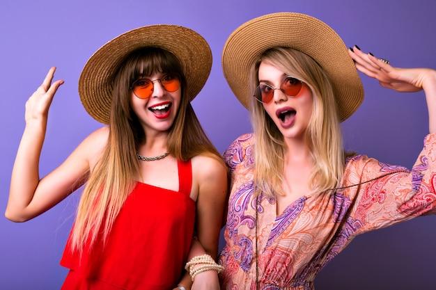 Vriendschap en communicatieconcept, twee zussen beste fronds meisjes dragen colocar bijpassende trendy zomer dressoir knuffels en kijkt op camera, boho bril, paarse achtergrond.
