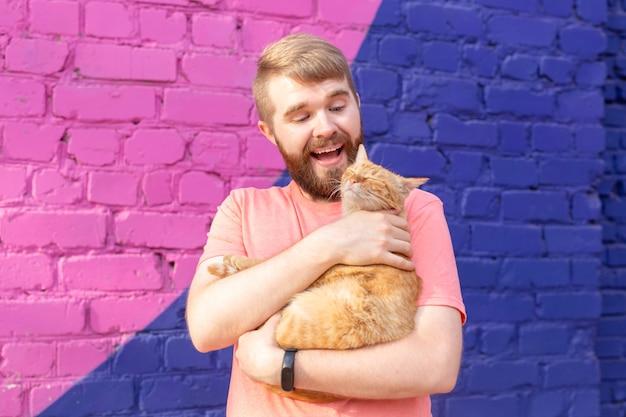 Vriendschap en huisdieren concept - knappe jonge man met schattige kat buitenshuis