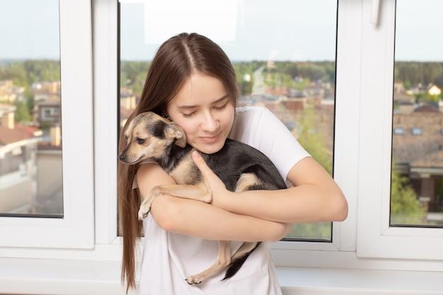 Vriendschap en liefde met een huisdier. meisje knuffelt haar kleine hond