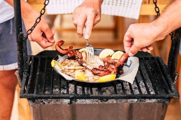 Vriendschap en mensen die vlees delen van een oude stijl vuur en hout barbecue bbq grill