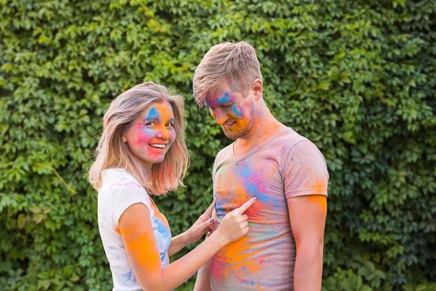 Vriendschap, festival van holi - jonge vrouw speelt met vuile t-shirt van jonge man op het festival van holi.