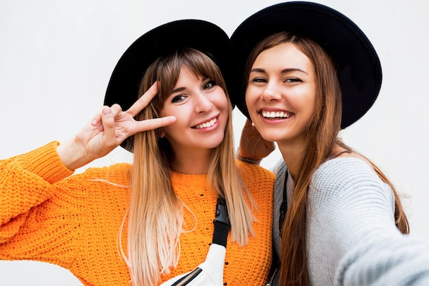 Vriendschap, geluk en mensenconcept. twee glimlachende meisjes die roddel op wit fluisteren